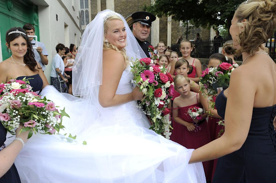 "<div class=""caption-credit""> Photo by: Rex USA</div><p> The bridesmaids, ages 2 to 17, all wore full-length, deep rose colored gowns with navy satin sashes. ""We chose the color of their dresses and the mums did a brilliant job of dressing the children,"" said the bride. </p>"