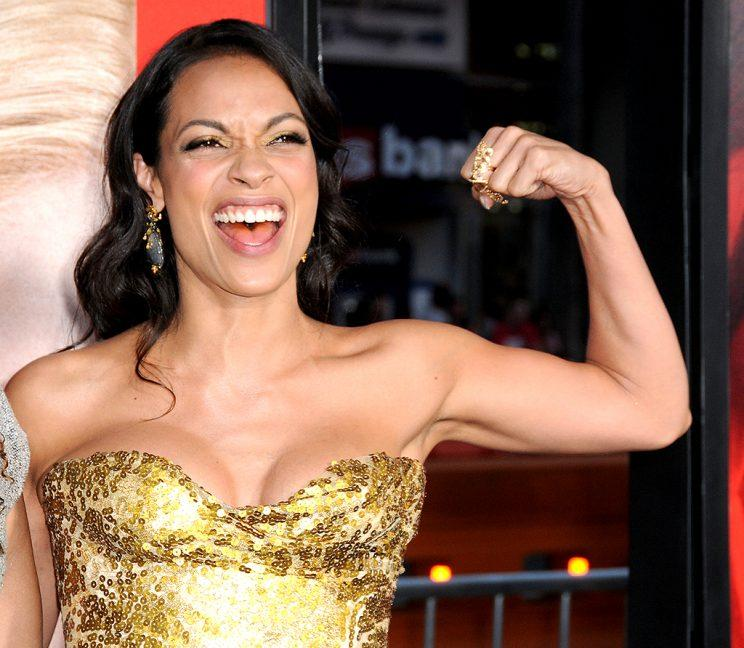 Rosario Dawson flexes her bicep in a gold sequin bustier.