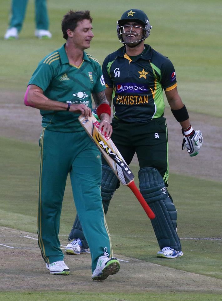 Pakistan's Umar Akmal laughs as South Africa's Dale Steyn jokingly takes his bat during their second Twenty20 cricket match in Cape Town, November 22, 2013. REUTERS/Mike Hutchings (SOUTH AFRICA - Tags: SPORT CRICKET)