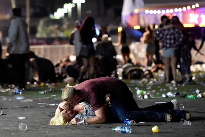 A man lies on top of a woman as others flee the Route 91 Harvest country music festival in Las Vegas on Oct. 1 after an active shooter was reported. (Photo: David Becker/Getty Images)