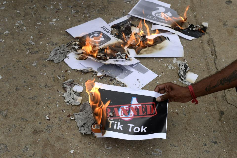 "Members of the City Youth Organisation burn posters with the logo of the Chinese owned video-sharing 'Tik Tok' app in support of the Indian government for banning the wildly popular app, in Hyderabad on June 30, 2020. - TikTok on June 30 denied sharing information on Indian users with the Chinese government, after New Delhi banned the wildly popular app citing national security and privacy concerns. ""TikTok continues to comply with all data privacy and security requirements under Indian law and have not shared any information of our users in India with any foreign government, including the Chinese Government,"" said the company, which is owned by China's ByteDance. (Photo by NOAH SEELAM / AFP) (Photo by NOAH SEELAM/AFP via Getty Images)"