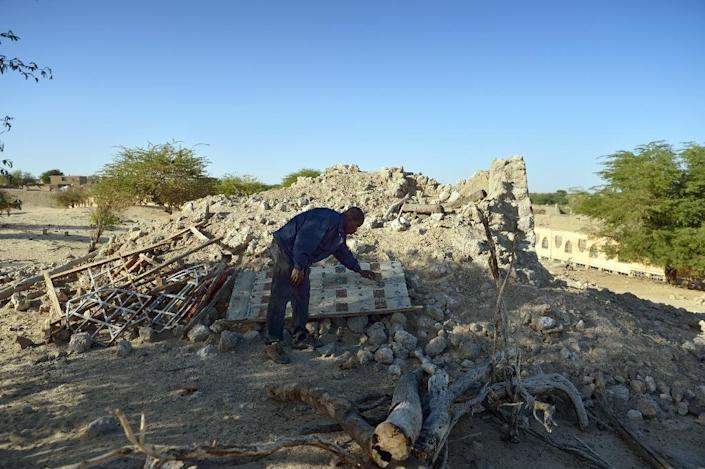 A man checking the ruins of the mausoleum of Alfa Moya, a Muslim saint, which was destroyed by Islamists in July 2013 in Mali's Timbuktu (AFP Photo/Eric Feferberg)