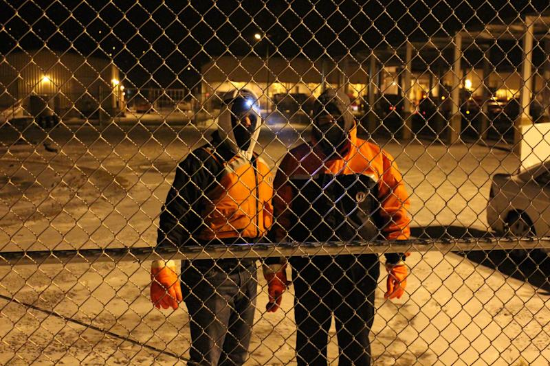 Danny Mayak, right, and his brother John Mayak, left, pause for a photograph while checking fuel on a barge Monday Jan. 6, 2014, at a petroleum products terminal in Coraopolis, Pa. As dangerously frigid air swept through this hard-luck Pennsylvania town on Monday night and early Tuesday morning, the few people who ventured outside needed something—a paycheck, a lottery ticket, a drink, or especially cigarettes. (AP Photo/Jesse Washington)