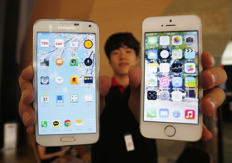 A sales assistant holding Samsung Electronics' Galaxy 5 smartphone and Apple Inc's iPhone 5 smartphone poses for photographs at a store in Seoul