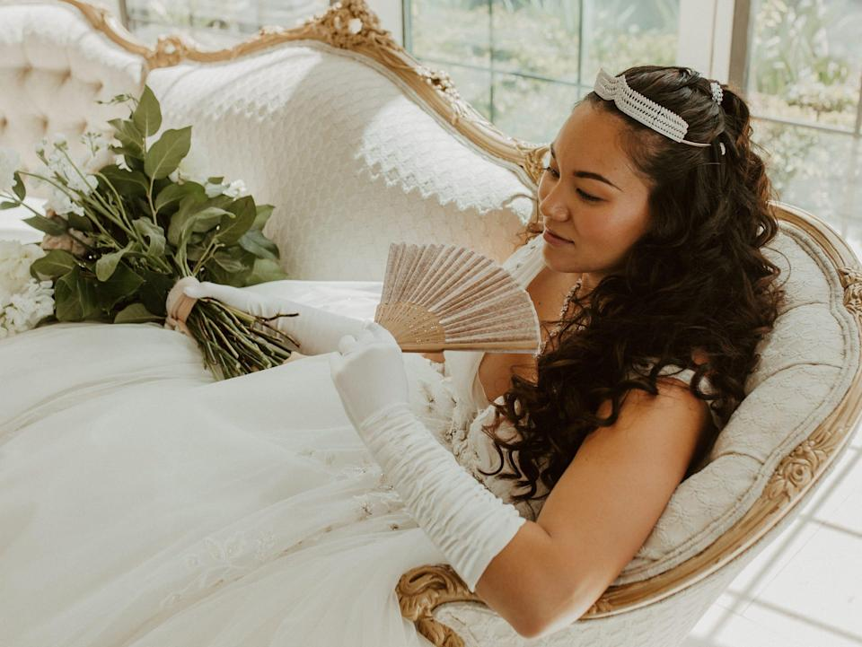 A bride sits on a white couch wearing gloves, a crown, and waving a fan.