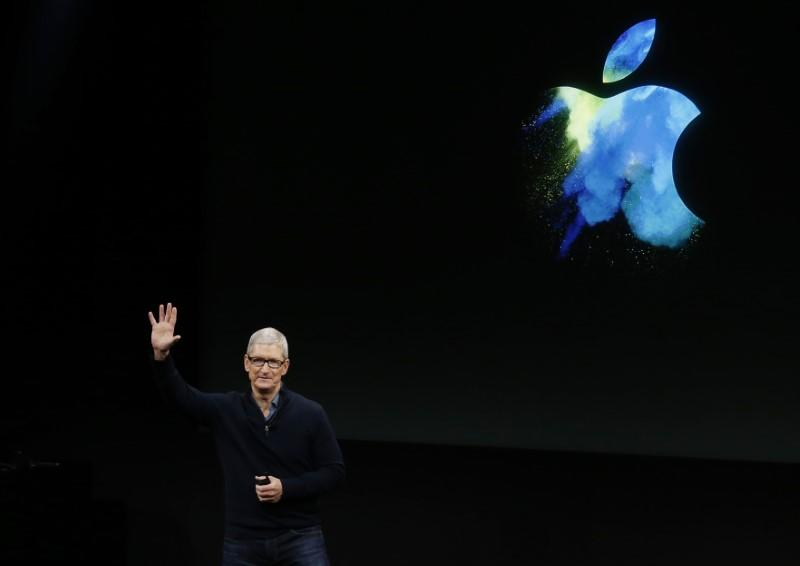 Apple CEO Tim Cook waves at the end of an Apple media event in Cupertino