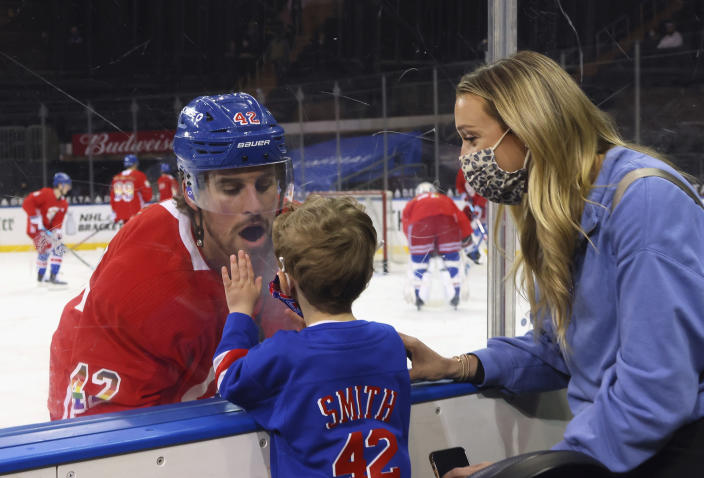 New York Rangers' Brendan Smith (42) says hello to his son Nolan and wife Samantha during warmups prior to an NHL hockey game against the Washington Capitals in New York, Monday, May 3, 2021. (Bruce Bennett/Pool Photo via AP)