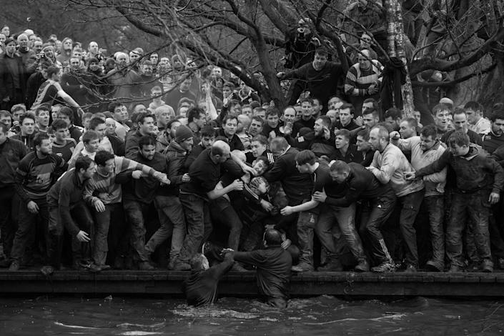 <p>Royal Shrovetide football: Members of opposing teams, the Up'ards and Down'ards, grapple for the ball during the historic, annual Royal Shrovetide Football Match in Ashbourne,Derbyshire, UK, Feb. 28, 2017.<br>The game is played between hundreds of participants in two eight-hour periods on Shrove Tuesday and Ash Wednesday (the day preceding and the day marking the start of Christian Lent). The two teams are determined by which side of the River Henmore players are born: Up'ards are from north of the river; Down'ards, south. Players score goals by tapping the ball three times on millstones set into pillars three miles apart.<br>There are very few rules apart from an historic stipulation that players may not murder their opponents, and the more contemporary requirement that the ball must not be transported in bags, rucksacks, or motorized vehicles. Royal Shrovetide Football is believed to have been played in Ashbourne since the 17th century. (Photo: Oliver Scarff/AFP) </p>