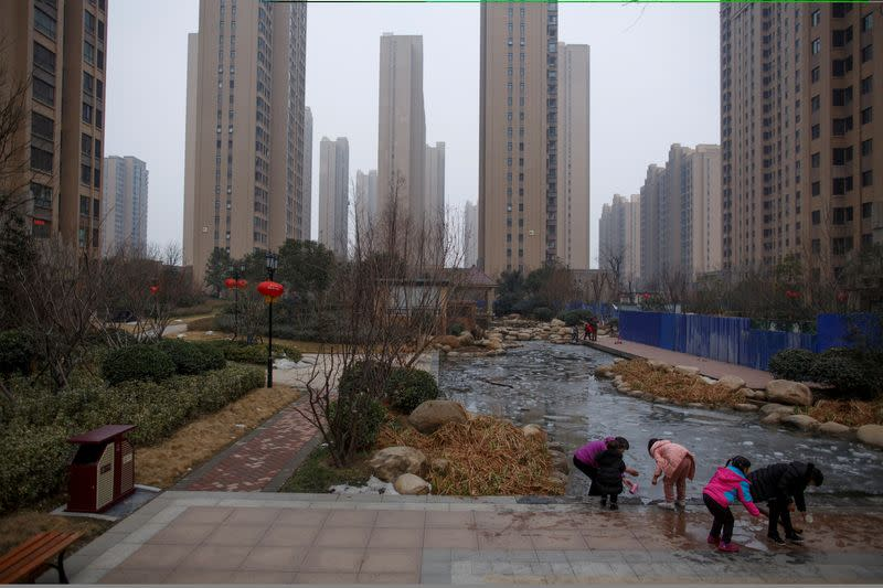 FILE PHOTO: People play with ice floats at a pond in the compound of a apartment complex in Zhengzhou