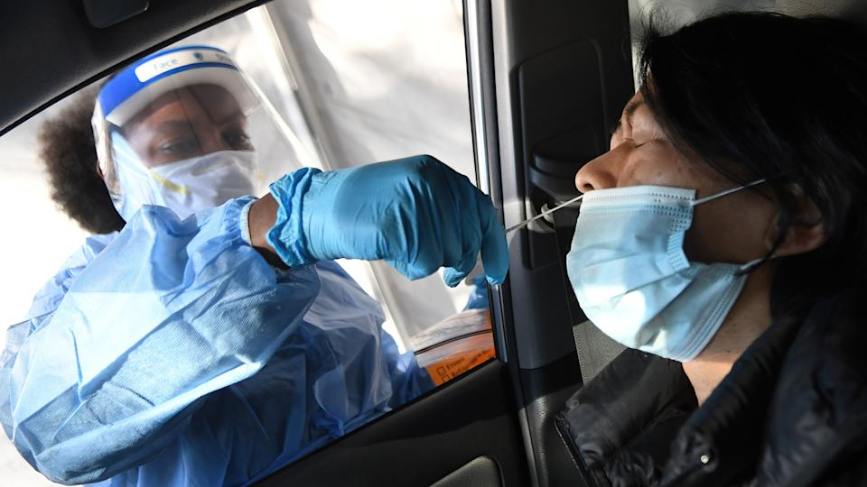 A medical worker performs a nasal swab on a woman at a rapid COVID-19 test site. (Paul Hennessy/SOPA Images/LightRocket via Getty Images)