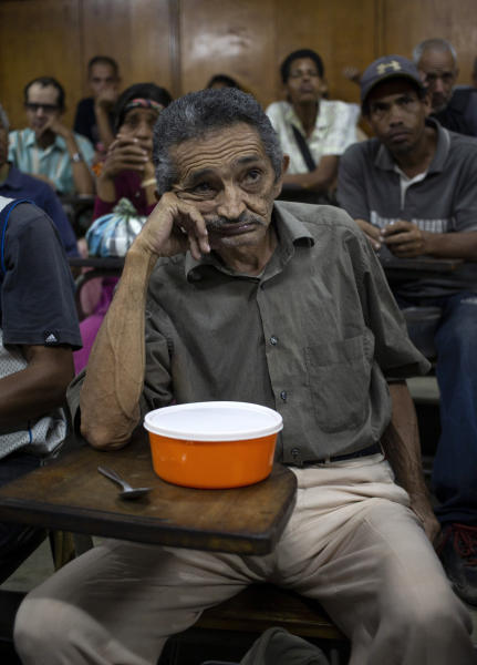 In this Feb. 27, 2020 photo, Orlando Blanco, 68, waits for food to be served at a religion center in the slum called The Cemetery in Caracas, Venezuela. In the midst of a severe crisis, families in Venezuela struggle to consume enough food daily. A recent study by the UN World Food Program reveals that one in three residents of the South American country has difficulty bringing food to the table and fails to meet their basic nutritional requirements. (AP Photo/Ariana Cubillos)