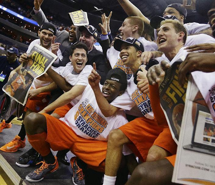 Syracuse players and coaches celebrate for photographers after their 55-39 win over Marquette in the East Regional final in the NCAA men's college basketball tournament, Saturday, March 30, 2013, in Washington. (AP Photo/Pablo Martinez Monsivais)
