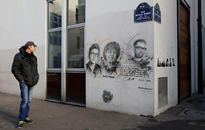 A man pauses outside the old offices of the satirical Charlie Hebdo magazine where two brothers armed with assault rifles shot and killed 11 people, including most of the publication's cartoonists and writers, on January 7, 2015, as France pays tribute two years later in Paris, France, January 5, 2017.  REUTERS/Jacky Naegelen