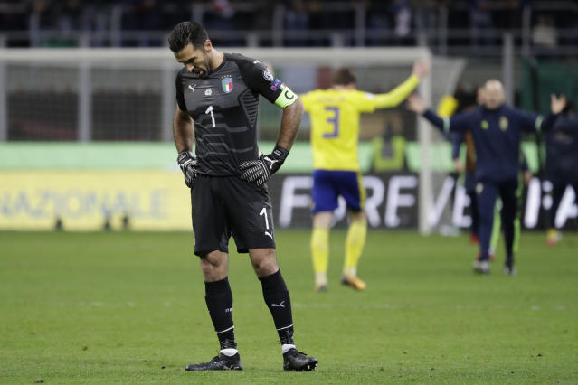 FILE - In this Monday, Nov. 13, 2017 file photo, Italy goalkeeper Gianluigi Buffon reacts to his team's elimination as Sweden players celebrate, rear, at the end of the World Cup qualifying play-off second leg soccer match between Italy and Sweden, at the Milan San Siro stadium, Italy. Gianluigi Buffon's international career might not be done after all. Interim Italy coach Luigi Di Biagio believes he has convinced the 40-year-old goalkeeper to stay on for friendlies against Argentina and England next month. (AP Photo/Luca Bruno, File)