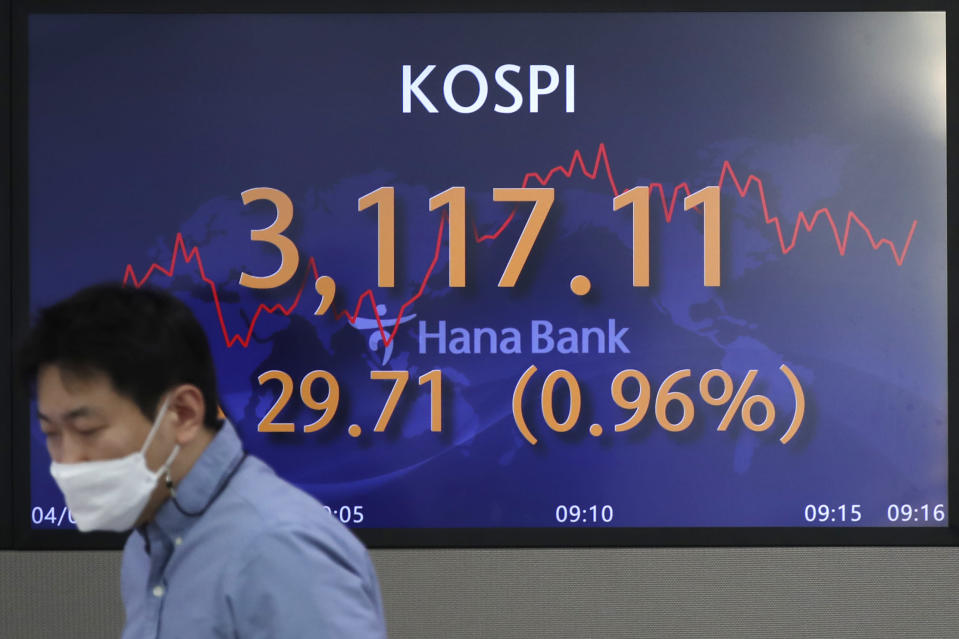 A currency trader walks near the screen showing the Korea Composite Stock Price Index (KOSPI) at the foreign exchange dealing room of the KEB Hana Bank headquarters in Seoul, South Korea, Friday, April 2, 2021. Asian shares were higher Friday after a broad rally pushed the S&P 500 past 4,000 points for the first time. (AP Photo/Lee Jin-man)