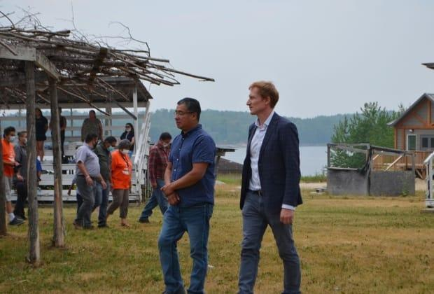 After signing the framework agreement on the Mercury Care Home in Grassy Narrows First Nation on Monday, Chief Randy Fobister and Indigenous Services Canada Minister Marc Miller walk around the powwow grounds. (Logan Turner / CBC - image credit)