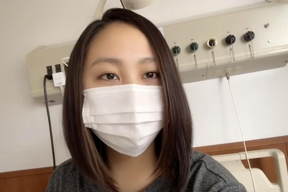 In this April 19, 2020, image made from the Youtube account of Arisa Kadono, she speaks to her smartphone video at a hospital, in Himeji, western Japan. Soon after Kadono tested positive for the coronavirus and hospitalized in early April, her friends let her know that groundless rumors were circulating. (Arisa Kadono via AP)