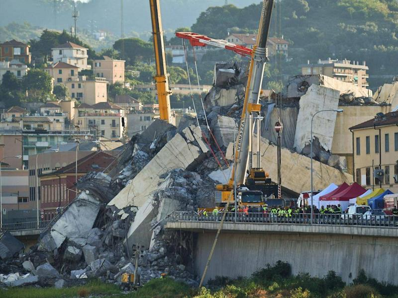Rescuers search the crumbled hulk of the collapsed Morandi highway bridge in Genoa, northern Italy, on Wednesday (ANSA via AP)