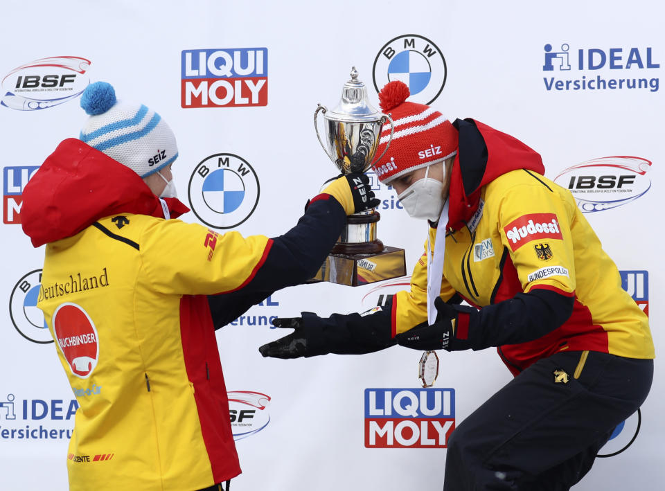 Second place, Germany's Jacqueline Loelling, left, hands the trophy to first place, Germany's Tina Hermann on the podium during the women's skeleton race at the Bobsleigh and Skeleton World Championships in Altenberg, Germany, Friday, Feb.12, 2021. (AP Photo/Matthias Schrader)