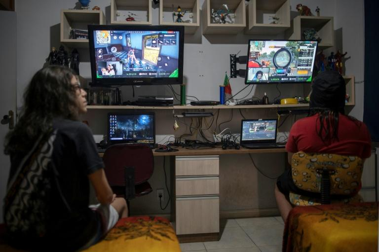 Brothers Guilherme (L), 14, and Arthur, 11, watch professional players from YouTube channel Loud play the mobile game Free Fire, at their house in Rio de Janeiro, Brazil (AFP Photo/Mauro PIMENTEL)