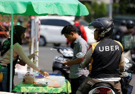 An Uber motorcycle taxi driver stops at a food stall next to a shopping mall in Jakarta, Indonesia September 20, 2017.  REUTERS/Darren Whiteside