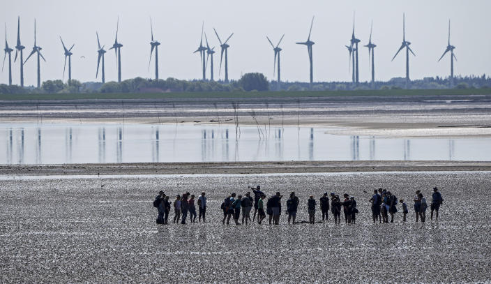 FILE - In this June 1, 2021 file photo, people explore the wadden sea at the island Norderney, Germany, in front of wind turbines, producing renewable energy. The cuts in greenhouse gas emissions pledged by governments around the world aren't enough to achieve the headline goal of the Paris climate accord, according to a United Nations report published Friday. The U.N. climate office said it reviewed all the national commitments submitted by Paris pact signatories until July 30 and found that they would result in emissions of planet-warming gas rising nearly 16% by 2030, compared with 2010 levels. (AP Photo/Martin Meissner, File)