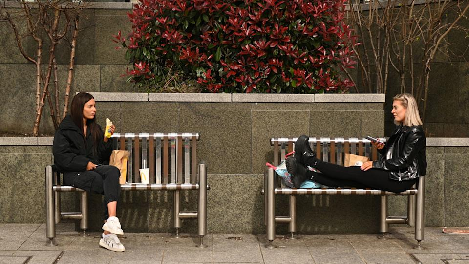 Two women sit apart, as it's revealed social distancing has helped reduce cases of the flu in Australia