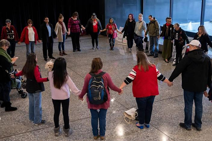 Protesters form a prayer circle in the lobby at the Sacramento County offices after disrupting a Board of Supervisors meeting over proposed COVID penalties on Tuesday, Dec. 8, 2020, in Sacramento.