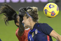 Argentina goalkeeper Solana Pereyra, left, knocks the ball away as United States midfielder Jaelin Howell attempts a header on goal off a corner kick during the second half of a SheBelieves Cup women's soccer match, Wednesday, Feb. 24, 2021, in Orlando, Fla. (AP Photo/Phelan M. Ebenhack)
