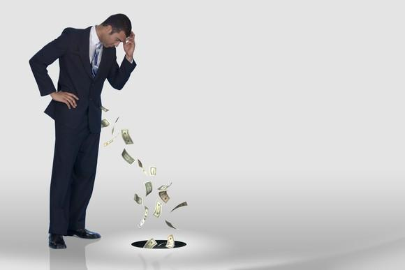 Money being sucked out of the pocket of a man wearing a suit.
