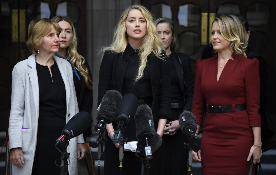 American actress Amber Heard, former wife of actor Johnny Depp, center, gives a statement after the end of the trial outside the High Court in London, Tuesday, July 28, 2020. Hollywood actor Johnny Depp is suing News Group Newspapers over a story about his former wife Amber Heard, published in The Sun in 2018 which branded him a 'wife beater', a claim he denies. (AP Photo/Alberto Pezzali)