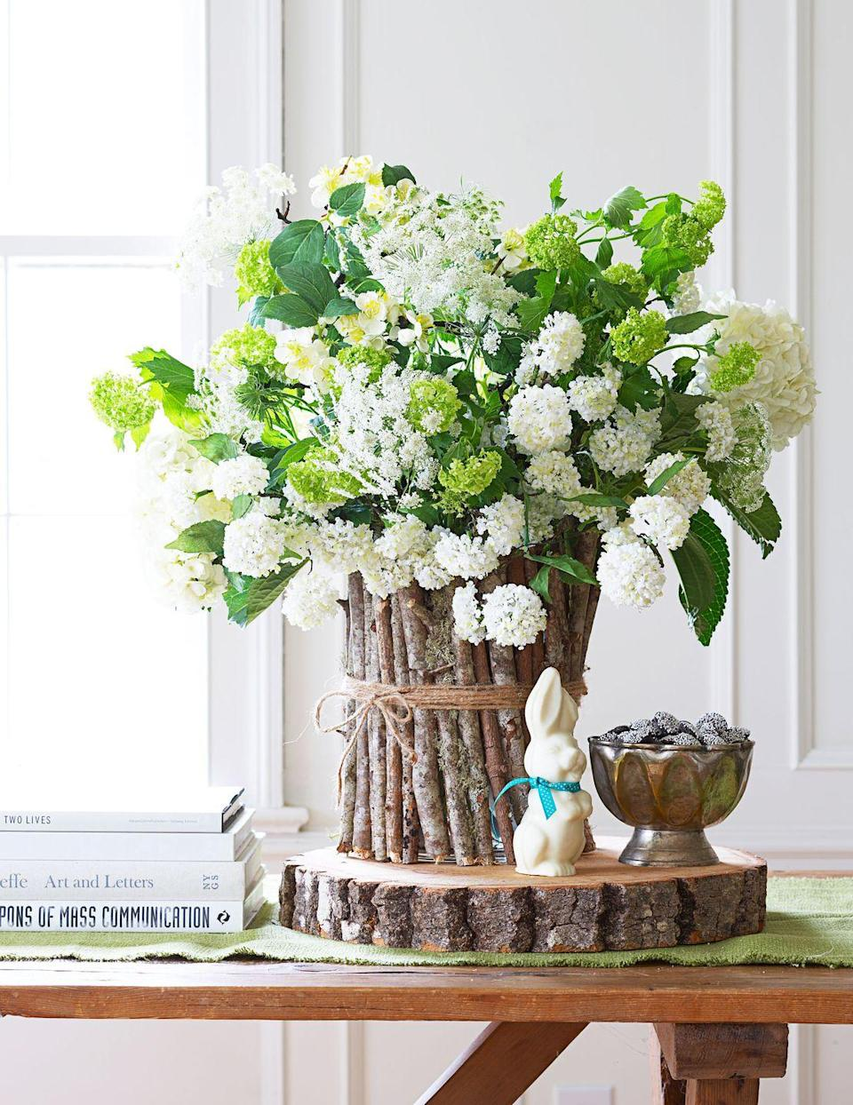 """<p>A woodsy vase echoes these flowers' country-garden vibe. For the container, cut 30 to 40 twigs to the height of a glass vase, then lightly hot-glue them to its surface, a few inches at a time. Finish with jute twine tied in a bow. For the flowers, bundle the hydrangeas first, then insert Queen Anne's lace. Keep fresh by misting.</p><p><a class=""""link rapid-noclick-resp"""" href=""""https://www.amazon.com/TIAMALL-Natural-Twine-String-Packing/dp/B01HEPXEE2?tag=syn-yahoo-20&ascsubtag=%5Bartid%7C10055.g.2217%5Bsrc%7Cyahoo-us"""" rel=""""nofollow noopener"""" target=""""_blank"""" data-ylk=""""slk:BUY TWINE"""">BUY TWINE</a></p>"""