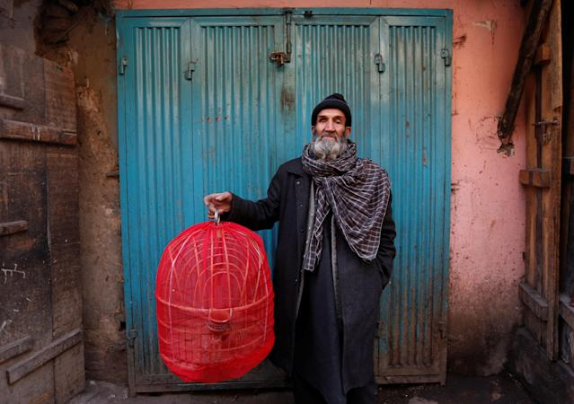 <p>Fatih, 70, holds a cage of partridges as he poses for a picture at Ka Faroshi bird market in Kabul, Afghanistan, Jan. 18, 2018. (Photo: Mohammad Ismail/Reuters) </p>