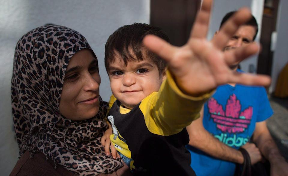 """<span class=""""caption"""">A Syrian refugee mother and her son attend an announcement in 2015 about a building being constructed to house and aid refugees, which opened a year later in Vancouver. </span> <span class=""""attribution""""><span class=""""source"""">THE CANADIAN PRESS/Darryl Dyck </span></span>"""