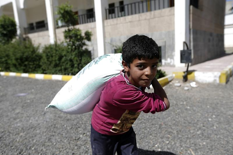 A Yemeni boy carries food aid distributed by a local charity during the Muslim holy fasting month of Ramadan, in the capital Sanaa, on May 29, 2017 (AFP Photo/Mohammed HUWAIS)