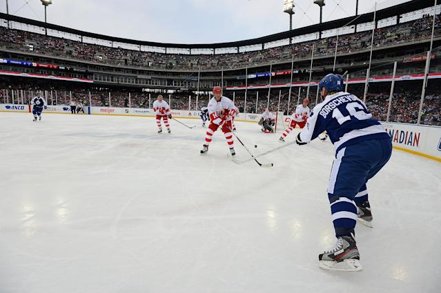 DETROIT, MI - DECEMBER 31: Nikolai Borschevsky #16 of the Toronto Maple Leafs passes the puck past the defense of Brent Fedyk #14 of the Detroit Red Wings in the first period during the 2013 Hockeytown Winter Festival Alumni Showdown on December 31, 2013 at Comerica Park in Detroit, Michigan. (Photo by Jamie Sabau/Getty Images)