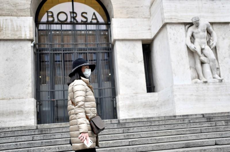 FILE PHOTO: Woman in a face mask is seen in front of the Italian Stock Exchange in Milan