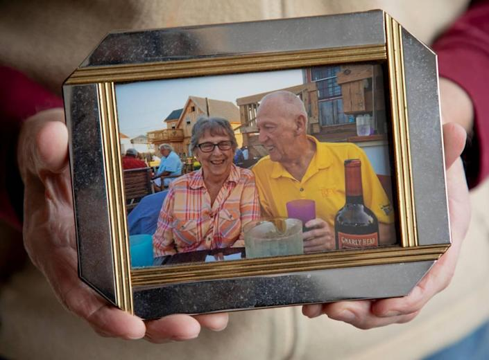 Albert Robinson holds a photograph of himself together with his wife, who died of complications from COVID-19, on Tuesday, Mar. 2, 2021, in Raleigh, N.C.