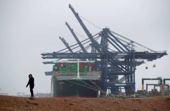 A view of the Port of Felixstowe as a person walks on the beach, in Felixstowe