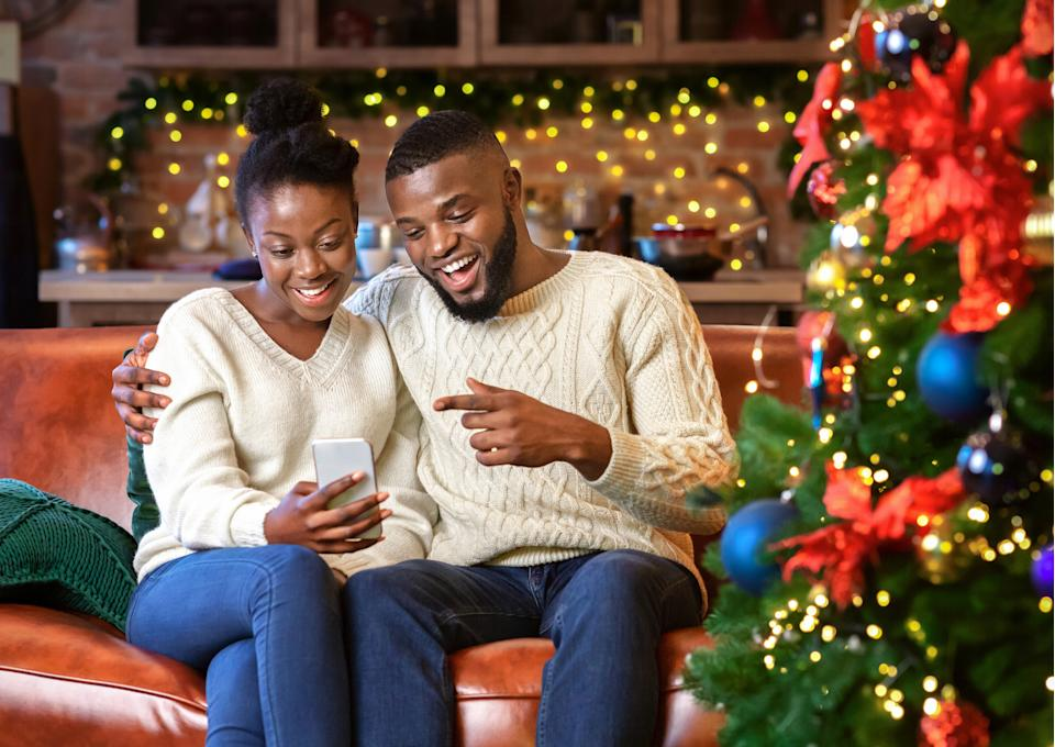 Happy african american couple making video call with smartphone, greeting their family with Christmas or New Year holidays.