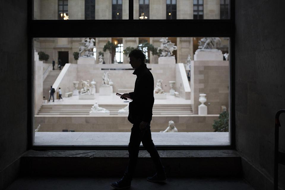 """A man checks his phone as he walks past the Louvre museum in Paris, Saturday, Feb. 4, 2017. The Louvre in Paris reopened to the public Saturday morning, less than 24-hours after a machete-wielding assailant shouting """"Allahu Akbar!"""" was shot by soldiers, in what officials described as a suspected terror attack. (AP Photo/Kamil Zihnioglu)"""