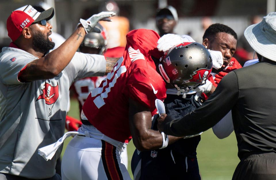 Tampa Bay Buccaneers wide receiver Antonio Brown (81) fights with Tennessee Titans defensive back Chris Jackson (35) during a joint training camp practice at AdventHealth Training Center Thursday, Aug. 19, 2021 in Tampa, Fla.