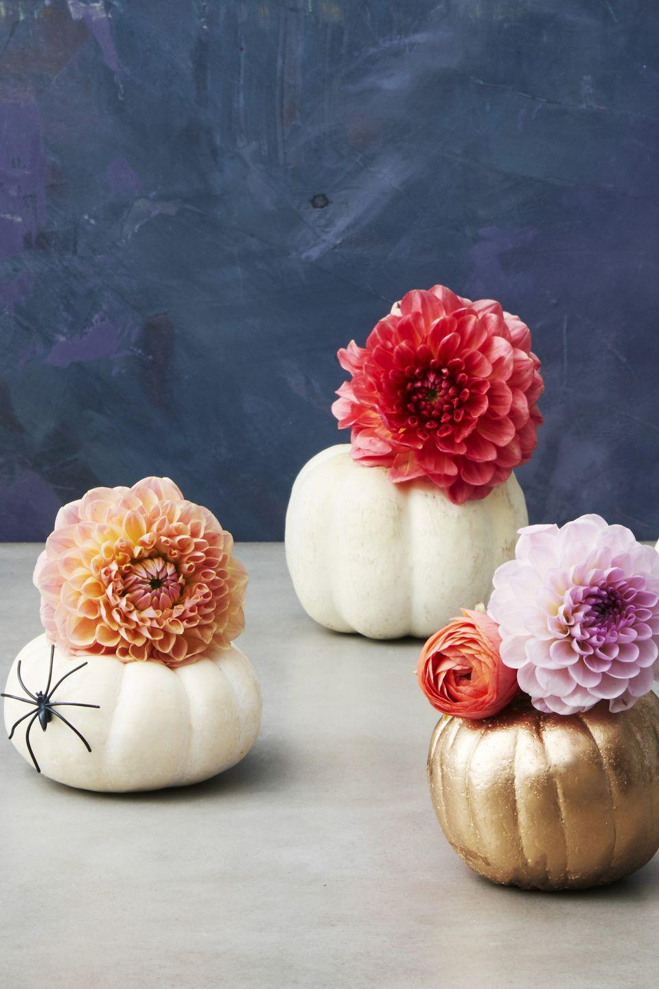 """<p>These <a href=""""https://www.goodhousekeeping.com/home/gardening/g22563541/fall-flowers/"""" rel=""""nofollow noopener"""" target=""""_blank"""" data-ylk=""""slk:flower-filled pumpkins"""" class=""""link rapid-noclick-resp"""">flower-filled pumpkins</a> are both adorable <em>and </em>practical. Paint mini pumpkins the color of your choice, carve off the top, add the bottom of a water bottle as a vase, and fill with fresh blooms. Then scatter them throughout your house, or use them to line the dinner table. </p>"""