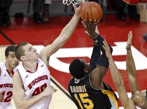 Wisconsin's Jared Bergrren (40) blocks a shot by Milwaukee's Demetrius Harris during the first half of an NCAA college basketball game Saturday, Dec. 22, 2012, in Madison, Wis. At right is Wisconsin's Ryan Evans. (AP Photo/Andy Manis)