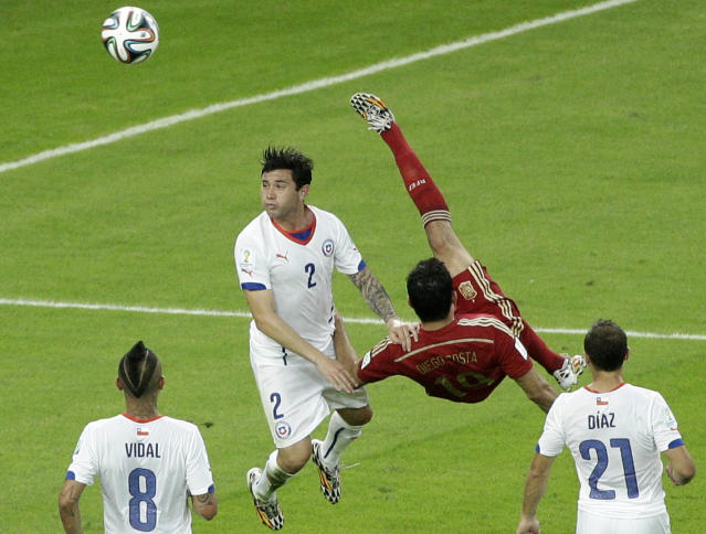 Spain's Diego Costa, second right, performs a bicycle kick next to Chile's Eugenio Mena during the group B World Cup soccer match between Spain and Chile at the Maracana Stadium in Rio de Janeiro, Brazil, Wednesday, June 18, 2014