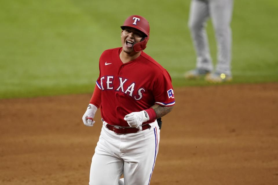 Texas Rangers' Yohel Pozo smiles as he rounds the bases on the way home after hitting a three-run home run in the sixth inning of the team's baseball game against the Oakland Athletics in Arlington, Texas, Friday, Aug. 13, 2021. The shot, that came off of relief pitcher Sergio Romo, scored Andy Ibanez and Jason Martin. (AP Photo/Tony Gutierrez)