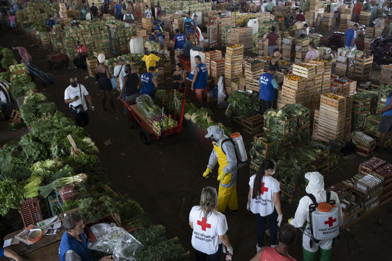 Members of the Red Cross disinfect a facility and distribute kits with cleaning products to workers at the CEASA, Rio de Janeiro's main wholesale market, amid the new coronavirus pandemic in Rio de Janeiro, Brazil, Tuesday, June 23, 2020. (AP Photo/Silvia Izquierdo)