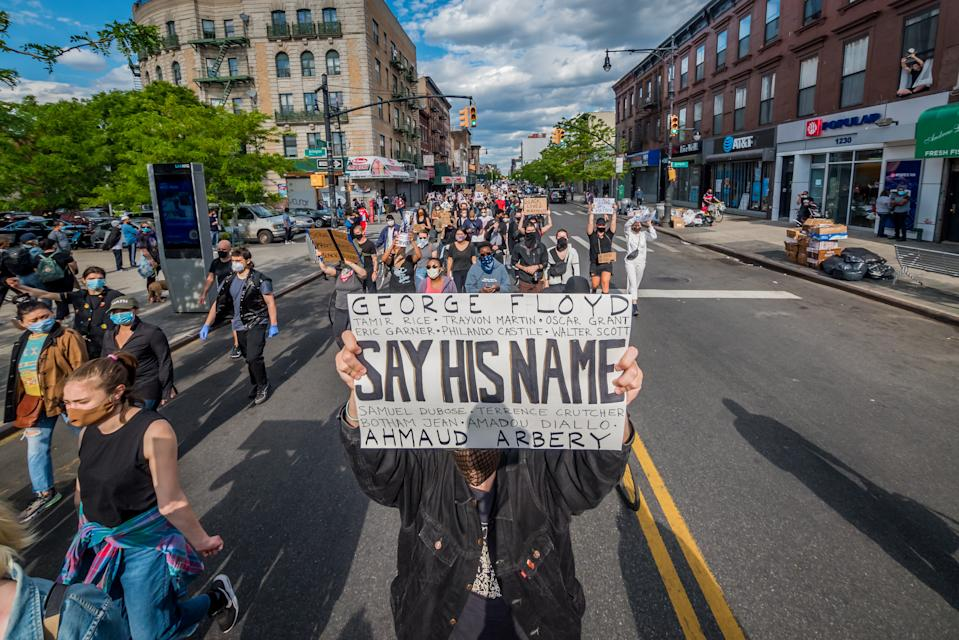"""A protester holding a """"Say His Name"""" sign in Brooklyn"""