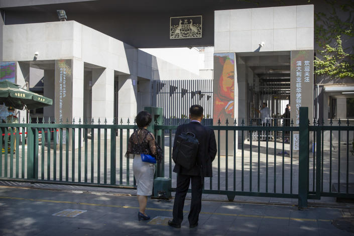 People stand at the gates of the Australian Embassy in Beijing, Tuesday, Sept. 1, 2020. Australia's government says a Chinese-born Australian journalist for CGTN, the English-language channel of China Central Television, has been detained in China. (AP Photo/Mark Schiefelbein)