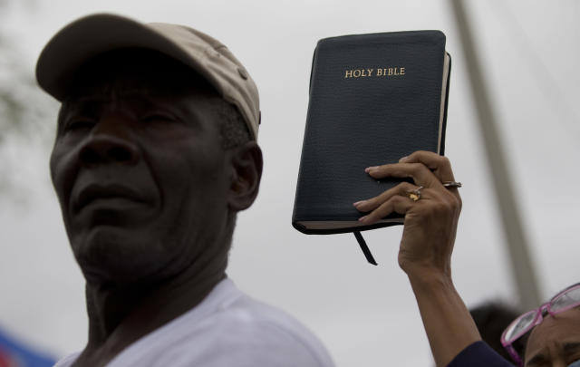 <p>Pastor Marie Belizaire, lower right, holds a bible as she listens to a news conference condemning President Trump's recent remarks denigrating Haiti, before a march to commemorate the eighth anniversary of the Haitian earthquake, Friday, Jan. 12, 2018, in Miami, Fla. (Photo: Wilfredo Lee/AP) </p>